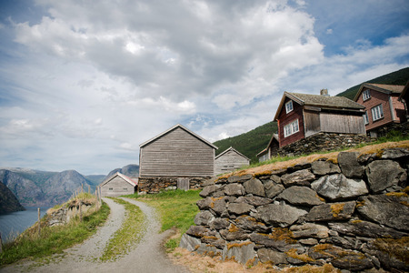 low angle view of stone wall, rural road and wooden houses at majestic Aurlandsfjord, Flam (Aurlandsfjorden), Norway Stock Photo