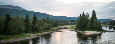 panoramic view of lake near forest and mountains in Trysil, Norways largest ski resort