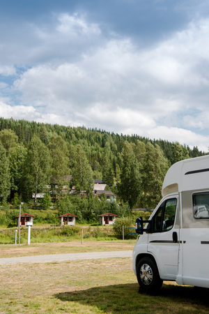 parked trailer near forest under cloudy sky in Trysil, Norways largest ski resort Stock Photo