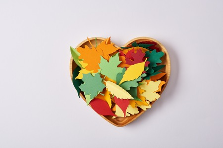 top view of wooden heart shaped box and colorful handcrafted leaves on white surface