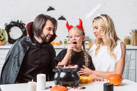 portrait of parents and daughter in halloween costumes at table with treats in black pot in kitchen at home