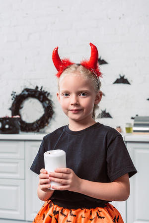 portrait of little kid with red devil horns holding candle in hands at home, halloween holiday concept