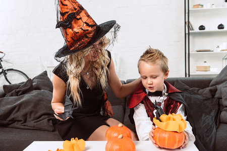 portrait of mother and son in halloween costumes sitting at coffee table with pumpkins at home