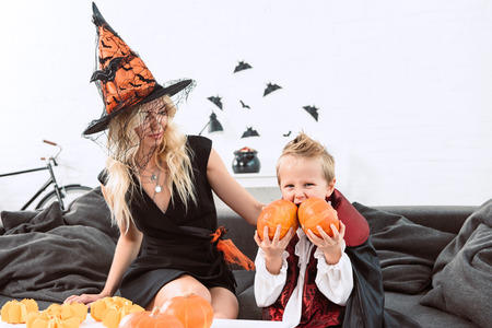 portrait of little boy in vampire halloween costume biting pumpkins sitting on sofa with mother in witch costume 写真素材