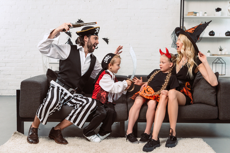 father and son in pirates costumes scaring mother and daughter on sofa at home 写真素材