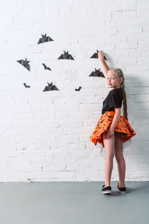 back view of child in skirt hanging black paper bats on white brick wall, halloween holiday concept