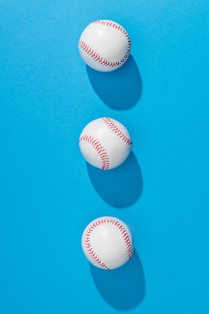 top view of arranged baseball balls on blue background