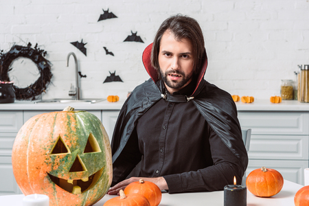 portrait of man in vampire halloween costume sitting at table with pumpkins in kitchen at home Stock Photo