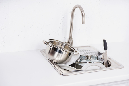 pile of dirty dishes in sink at kitchen