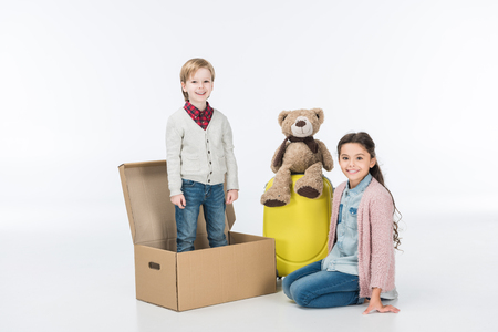 Little boy standing in cardboard box ready to move with his sister into new house isolated on white
