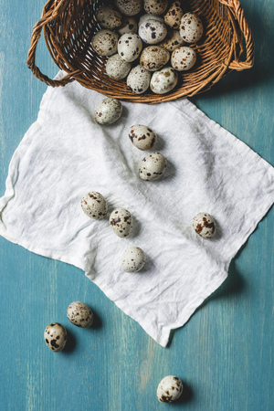 top view of raw healthy quail eggs in wicker basket and white cloth on turquoise wooden table