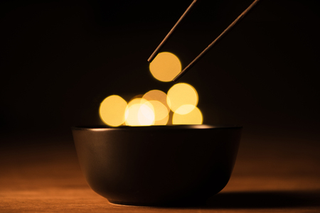 close up view of bowl, chopsticks and bokeh lights on black background