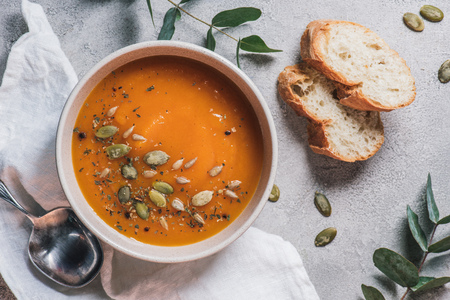 top view of bowl with pumpkin cream soup with seeds and bread on table Stock Photo