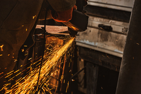 partial view of worker using circular saw with sparkles at factory