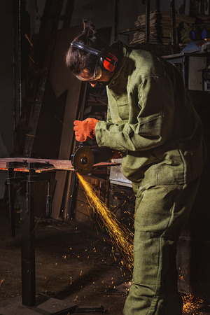 manufacture worker in protective googles working with circular saw at factory Imagens