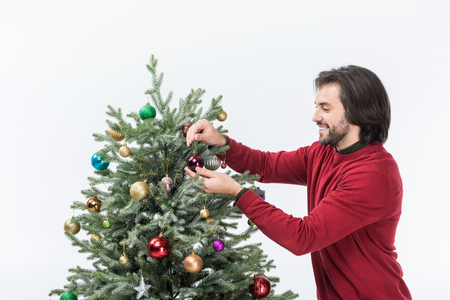 smiling man decorating christmas tree with glass balls isolated on white