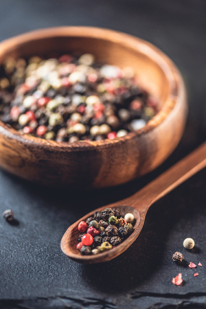 close-up view of wooden spoon and bowl with dried aromatic peppercorns on black