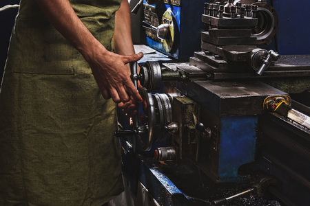 cropped image of male manufacture worker in protective apron using machine tool at factory