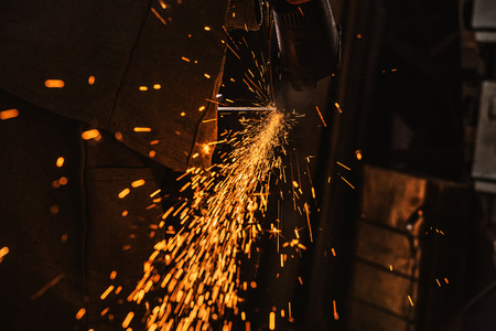 cropped image of manufacture worker using circular saw with sparkles at factory