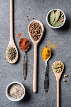 top view of different dried aromatic spices in spoons and bowls on grey  background