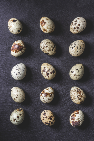 top view of raw organic unshelled quail eggs on black
