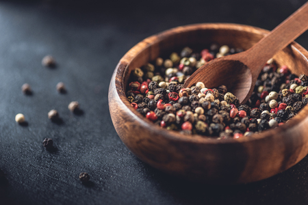 close-up view of wooden bowl and spoon with dried aromatic peppercorns on black