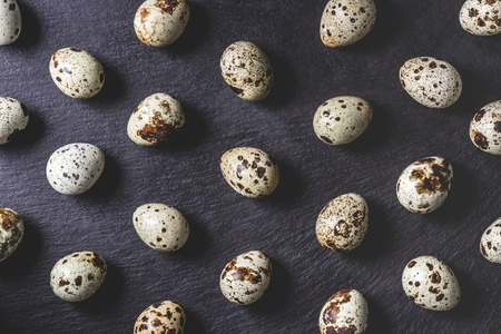 top view of organic unshelled quail eggs on black background, seamless pattern Standard-Bild