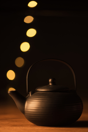 close up view of clay teapot and golden bokeh lights as steam on black background Standard-Bild - 109025249