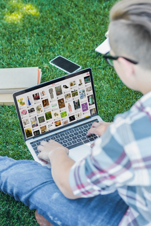 cropped shot of teenager using laptop with pinterest website while sitting in park