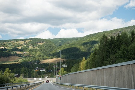TRYSIL, NORWAY - 26 JULY 2018: road with cars near forest and mountains at largest ski resort Trysil in Norway Editorial