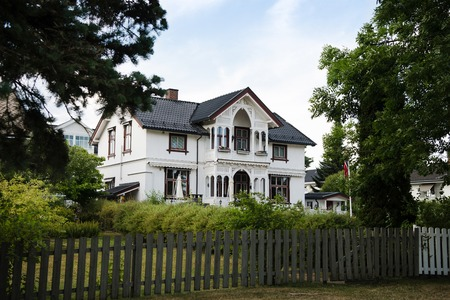 HAMAR, HEDMARK, NORWAY - 26 JULY 2018: wooden fence and beautiful living house 新闻类图片