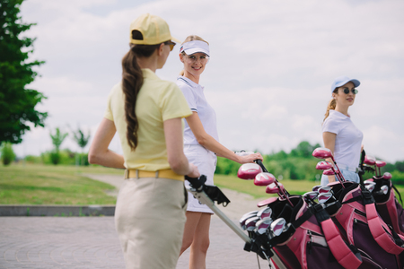 selective focus of female golfers with golf equipment walking at golf course Stok Fotoğraf