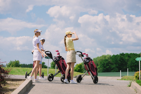 female golfers with golf equipment walking at golf course