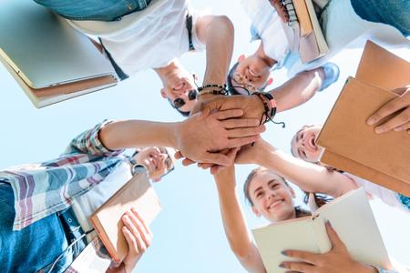bottom view of happy multiethnic teenage classmates stacking hands in park 写真素材 - 110833684