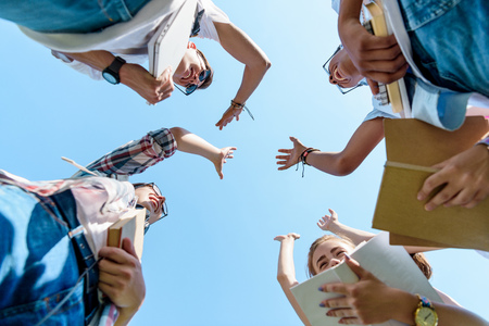 bottom view of happy multiethnic teenage classmates giving high five in park