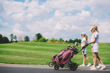 side view of female golfers with golf equipment walking at golf course Stok Fotoğraf