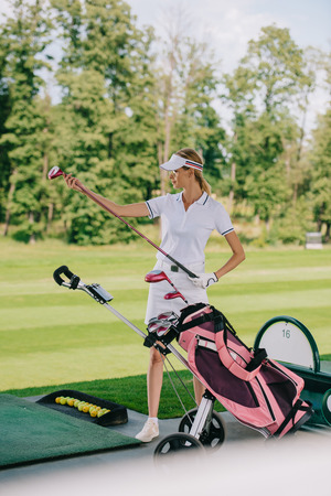 female golf player in cap with golf gear at golf course