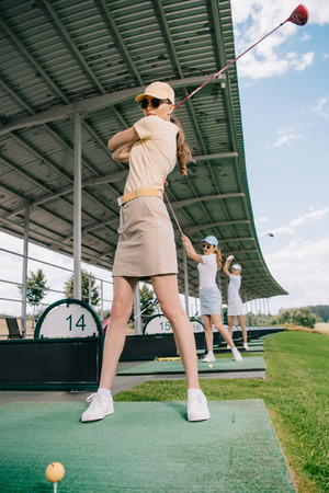 low angle view of women with golf clubs playing golf at golf course Stok Fotoğraf