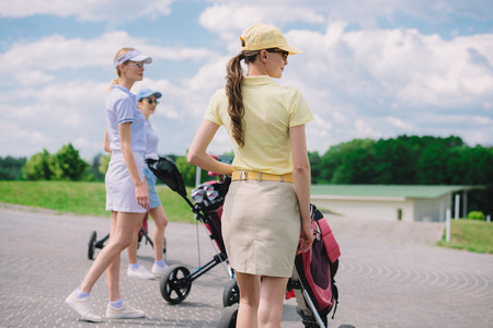 selective focus of female golfers with golf equipment walking at golf course 写真素材