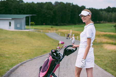 selective focus of smiling female golf player in cap and white polo with golf gear at golf course Stok Fotoğraf