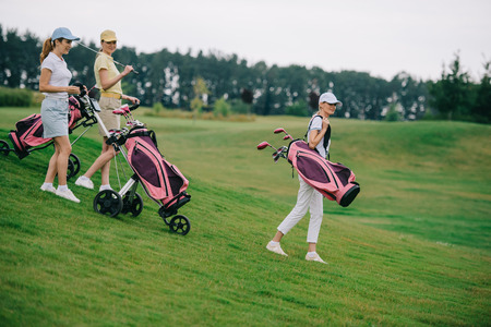 side view of women in polos and caps with golf gear walking on green lawn at golf course