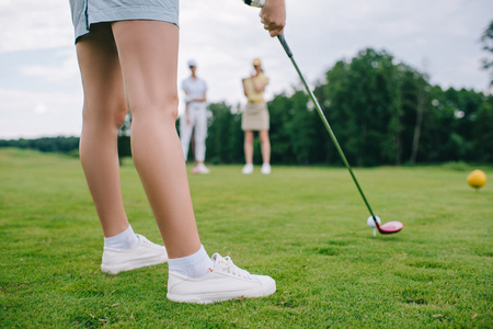 cropped shot of woman playing golf while friends standing near by at golf course