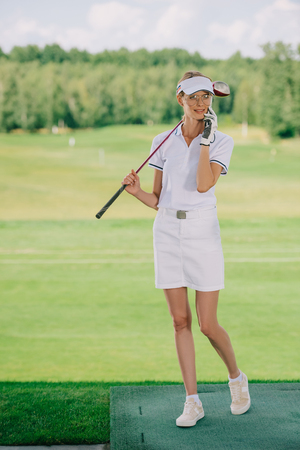 female golf player in polo and cap with golf club in hand talking on smartphone at golf course