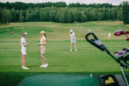 selective focus of women in caps with golf equipment at golf course