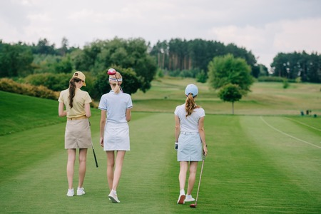 rear view of women in caps with golf equipment walking at golf course