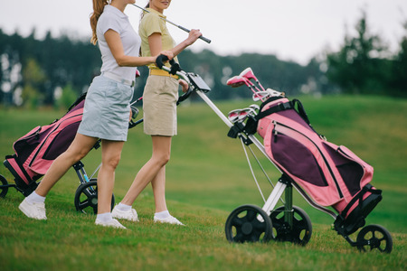 partial view of female golf players in polos walking on golf course Stok Fotoğraf - 109044939