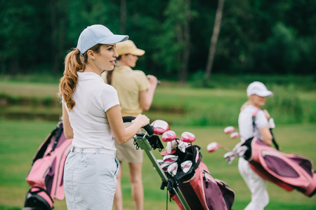 selective focus of women in caps with golf gear walking on green lawn at golf course