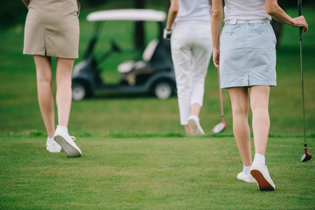 cropped shot of women with golf clubs walking on green lawn at golf course