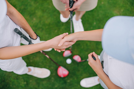 overhead view of female golf players with golf clubs shaking hands while standing on green lawn Stok Fotoğraf - 109044980