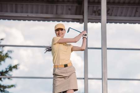 portrait of smiling female golf player in cap with golf club in hands